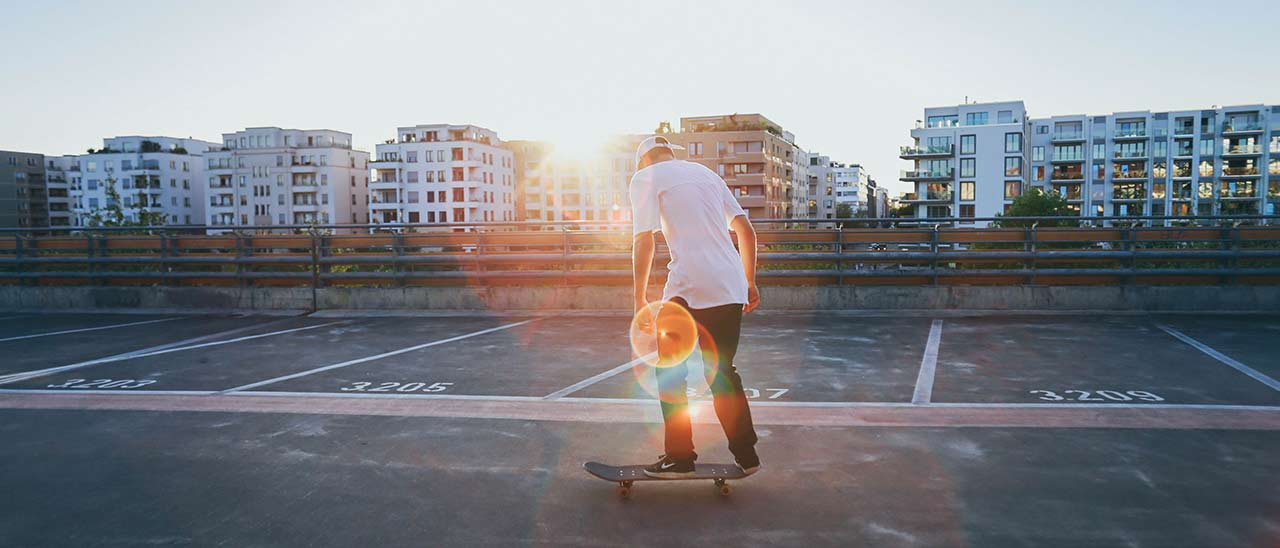 Photo of a skater with glaring sunset in the background in front of tower buildings who enjoys his hobby